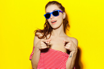Beautiful young sexy girl in blue sunglasses and a red striped T-shirt laughing and having fun on a yellow background