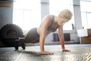 Attractive young woman wrapped up in fitness training: she doing plank exercise and looking down with concentration, full-length portrait