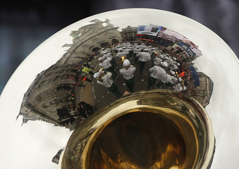 Piccadilly circus is reflected in a brass instrument of a marching band from the U.S. during the annual New Year's Day Parade through Parliament Square in central London