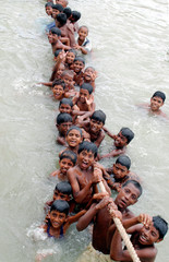 Bangladeshi children bathe while hanging onto rope on bank of Buriganga river in Dhaka.