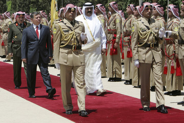Jordan's King Abdullah and Emir of Qatar Sheikh Hamad bin Khalifa al-Thani review Bedouin guard of honour upon Sheikh Hamad's arrival at Amman airport