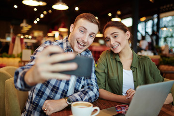 Leaving in memory warm evening with friend: pretty young woman and handsome bearded man taking selfie on smartphone while sitting in cozy coffeehouse