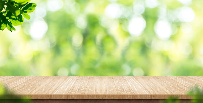Empty wood plank table top with blur park green nature background bokeh light,Mock up for display or montage of product,Banner or header for advertise on social media,Spring and Summer concept