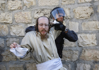 An Israeli policeman pulls back an ultra-Orthodox Jew during a protest in Jerusalem