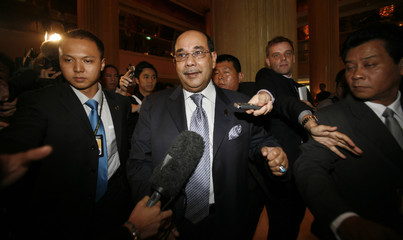 Malaysia's FM Syed Hamid Albar is surrounded by journalists during the 13th ASEAN Summit in Singapore