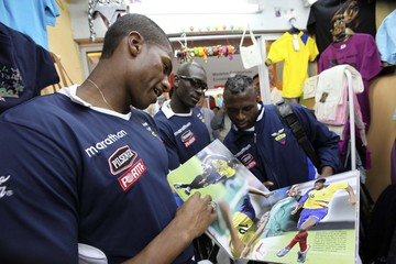 Ecuadorean soccer players Antonio Valencia, Alejandro Castillo and Cristian Benitez look at a magazine at Mariscal Sucre airport in Quito
