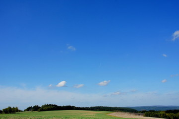 blauer Himmel mit wenigen Wolken über herbstlichen Feldern im Hunsrück