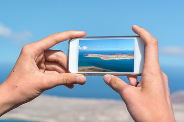 Close up on hands holding a smartphone to take pictures, in Lanzarote, Spain
