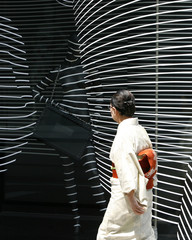A woman clad in kimono walks past a luxury brand store in a Tokyo shopping district