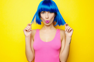 Beautiful young sexy girl in blue wig and pink swimsuit is having fun and fooling around on yellow background