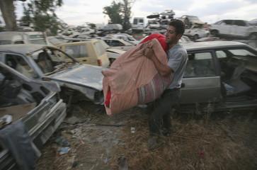 Palestinian labourer carries a blanket in Beersheba