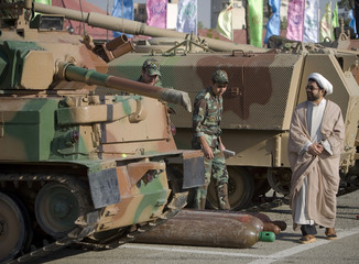 Cleric looks at a tank while visiting a war exhibition in central Tehran