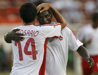Dwayne DeRosario of Canada congratulates teammate Ali Gerba after scoring against Guadeloupe during their CONCACAF Gold Cup soccer match at the Orange Bowl in Miami