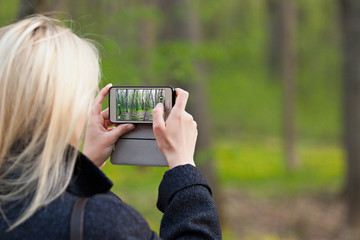 Girl takes pictures of the spring forest on the camera phone