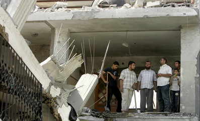 People inspect the damaged house of Mariam Farhat after it was hit by an Israeli missile in Gaza
