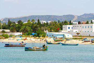 Blick auf den Strand und das Meer bei Hammamet mit Fischerbooten im Wasser.