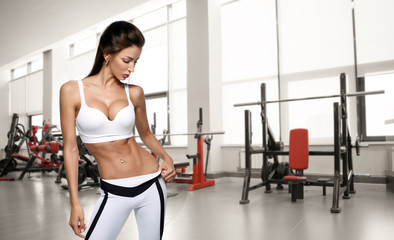 Young beautiful athlete woman in the gym