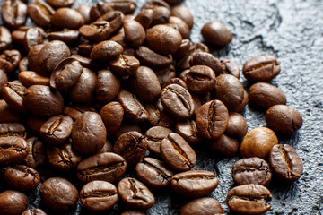 Grains of coffee are scattered on a black stone
