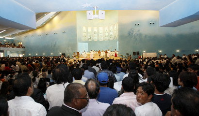 People stand inside during first mass at St Mary's Roman Catholic church in Doha