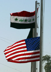The Stars and Stripes flies at half mast, after a dawn ceremony in which the Iraqi flag was raised f..