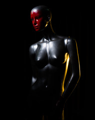 Silver female fashion mannequin with red face over black background