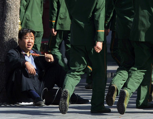 A CHINESE MAN IS SURPRISED TO SEE POLICEMEN MARCH PAST IN BEIJING.