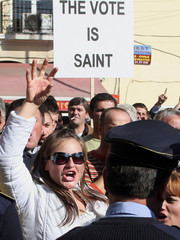 Citizens shout anti-government slogans during a demonstration outside the parliament building in Tirana
