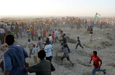 Palestinian youths run towards fence of Jewish settlement of Neve Dekalim, from Khan Younis in the ...