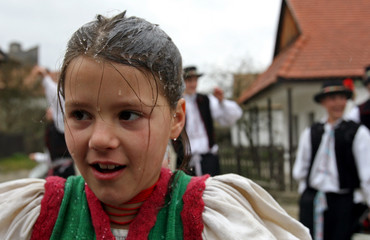 A girl reacts after boys threw water at her as part of traditional Easter celebrations in Holloko