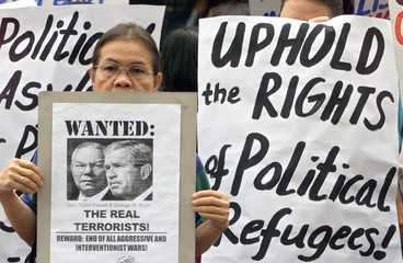 A FILIPINO PROTESTER DISPLAYS A SIGN CONDEMNING U.S. PRESIDENT BUSH ANDSECRETARY OF STATE ...