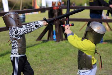 Fototapeta Dwóch chłopców w zbrojach rycerskich walczą na miecze. obraz