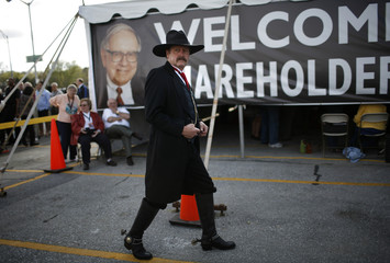A man dressed as a cowboy welcomes Berkshire Hathaway shareholders to a barbeque at their annual shareholders' meeting in Omaha, Nebraska