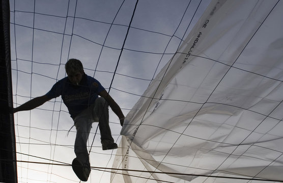 A worker pulls a plastic sheet over the top of a greenhouse under-construction in El Ejido