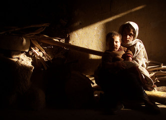 AFGHAN GIRL HOLD HER BROTHER IN THEIR HOME IN KABUL.