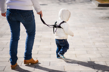 Mom insures her child during a walk