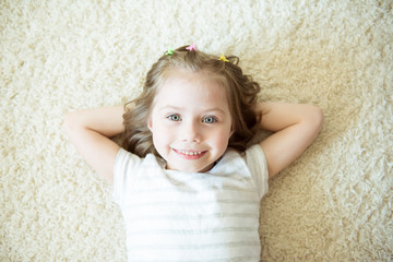 Smiling girl on a white carpet. Portrait