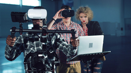 Young people testing camera gyro stabilizer gimbal with virtual reality headset on, looking around. Men and woman with laptop