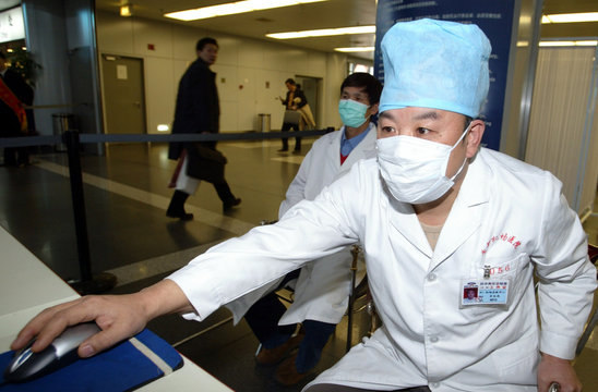 A MASKED CHINESE MEDICAL WORKER CONTROLS A THERMAL-IMAGING THERMOMETER TO MONITOR TRAVELLERS' ...