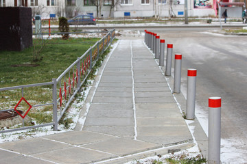 Fencing of the sidewalk from cars several metal posts, antiterrorist protection