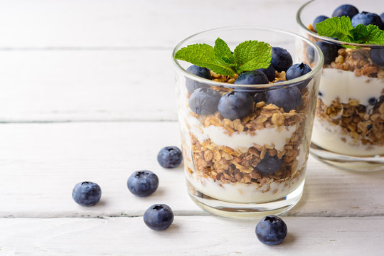 Granola with yogurt and blueberries in glass on white wooden table.