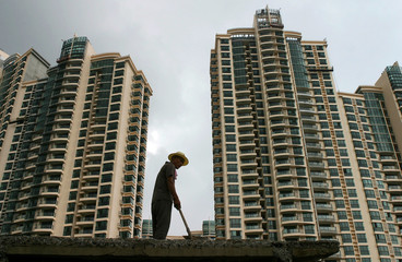 A Chinese labourer works near a new luxurious residential property in Shanghai.