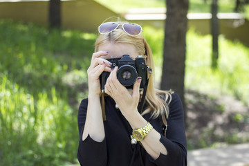Girl with old photo camera in a park