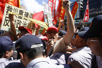 Protesters against the Dalai Lama scuffle with the police outside his hotel in Taipei, Taiwan