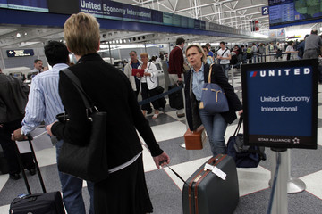 Customers wait to check-in at United Airlines terminal at O'Hare International Airport in Chicago