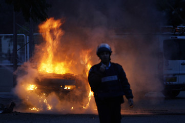 Israeli police officer stands in front of burning car in Ashkelon