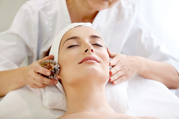 Spa salon: Beautiful Young Woman having Facial Massage with Shell.