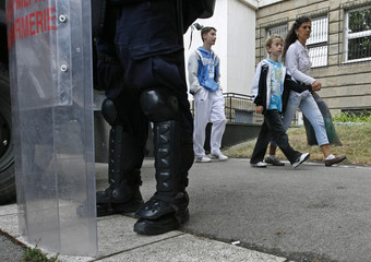 People pass by a member of the Serbian Gendarmerie guarding the Special Court building in Belgrade
