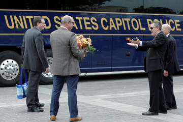 Members of Congress and staffers board buses to leave Capitol Hill