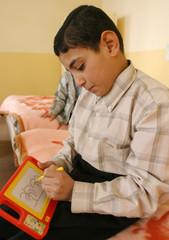 Iraqi orphan draws plam tree at an orphanage in Basra.