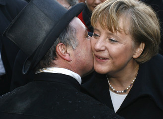 German Chancellor Merkel is kissed by a chimney sweeper during her visit at the 50th anniversary of the southwestern German state of Saarland in Merzig